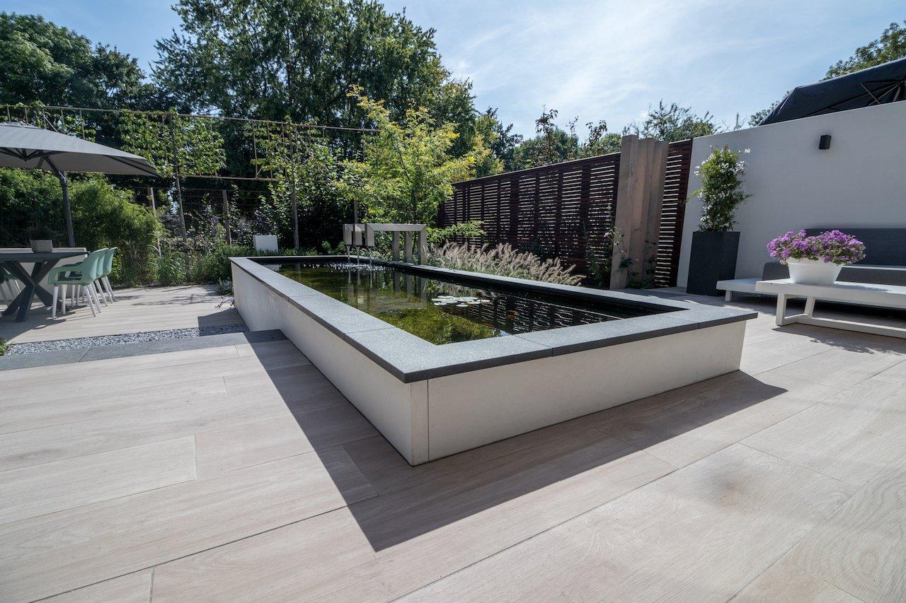 Royale achtertuin met zwemvijver en organische cortenstaal rand.